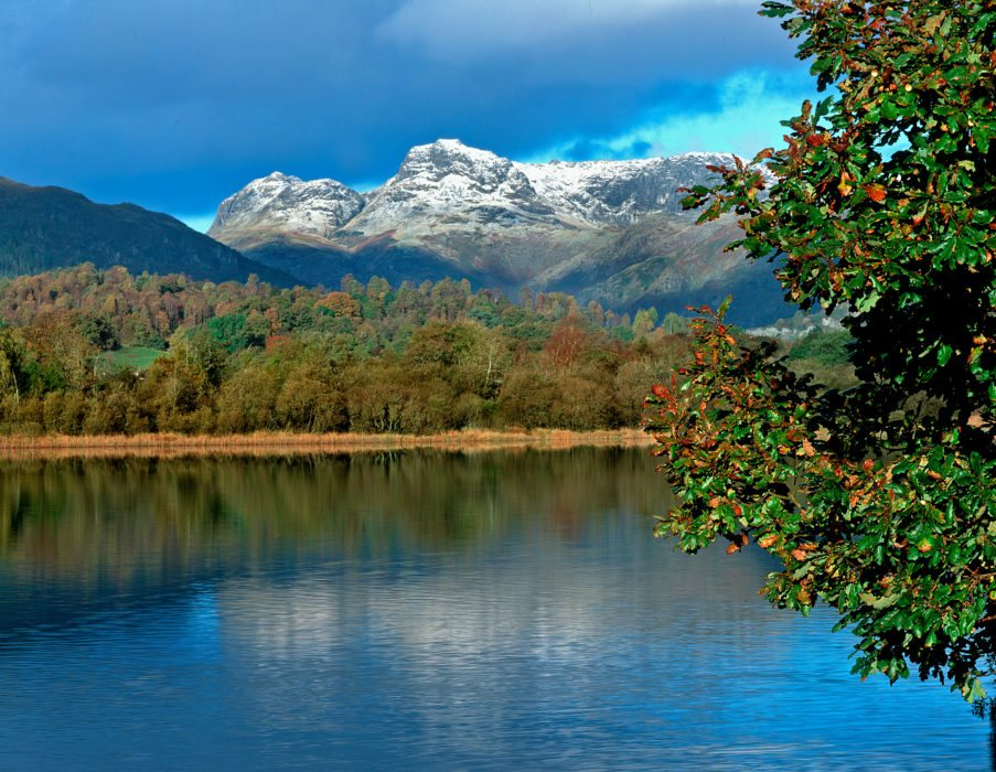 Elterwater with autumnul trees and the snow capped Langdale Pikes behind