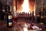 Image of a roaring Log Fire and a bottle of wine