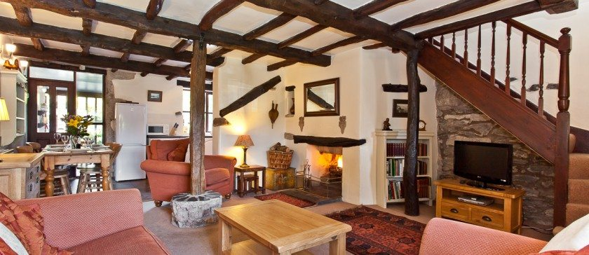 The sitting room in Carree Cottage and the roaring log fire