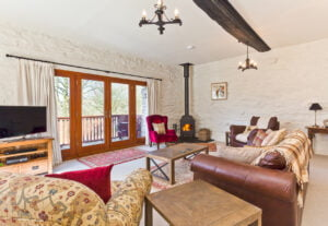 The sitting room, log fire and balcony at Charcoal House